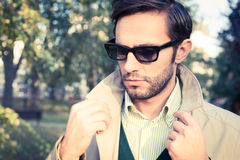 Trench coat. Handsome man wearing trench coat in park Royalty Free Stock Photos