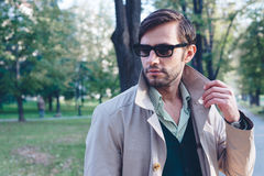 Trench coat. Handsome man wearing trench coat in park Stock Photo