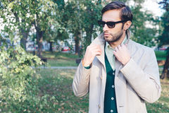 Trench coat. Handsome man wearing trench coat in park Royalty Free Stock Image