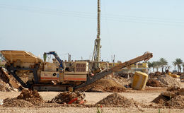 Trench digger. With pile driver in the background on a large construction site Royalty Free Stock Photo