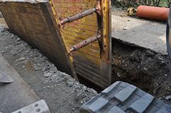 Trench digging in building site. Trench digging excavator in a construction building site stock images