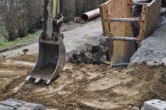 Trench digging in building site. Trench digging excavator in a construction building site royalty free stock images