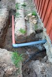 Trench near house with water and sewerage pipes. Trench near wooden village house with water and sewerage pipes Stock Photography