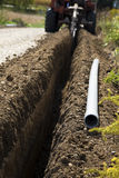 Trencher in action. Focus on the pvc conduit Royalty Free Stock Images