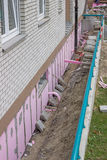 Trenching around building for new layer of foam insulation. Fitting styrofoam thermal insulation Stock Photography