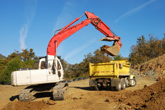 Trenching. Large track hoe exchavator filling a dump truck at a new commercial construction site in Roseburg Oregon Stock Image