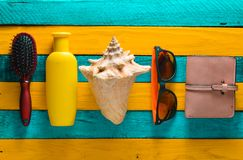 Trend accessories for relaxation on the beach and beauty on a yellow blue wooden table. Purse, comb, sunglasses, shell, sunblock. Stock Photos