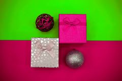 Pink and silver balls and gift boxes with a bow on a color background royalty free stock images