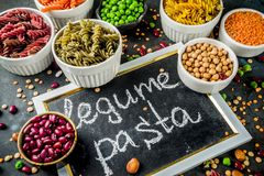 Various legume pasta. Trend healthy food, vegan diet concept. Multi colored legume pasta with raw beans. Beans, chickpeas, green peas, lentils. Copy space top royalty free stock photo