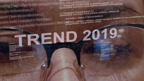 Trend 2019 text on background of female developer. Trend 2019 text on the background of female software developer. Eyes of woman with glasses are looking at stock video