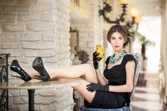 Trendig attraktiv ung kvinna i svart sitta för klänning som är bekvämt i restaurang Brunett som kopplar av med ben på tabellen Royaltyfri Fotografi