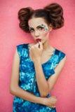 Trendig bild av den trendiga modellen med bullen för två hår och idérik yrkesmässig makeup som poserar på rosa bakgrund Idérikt g Arkivfoton