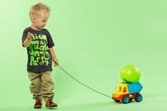 Trendig blond gullig pojke som drar den plast- bilen Royaltyfri Bild