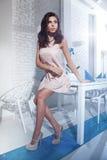 Trendig brunettflicka som poserar i modern inre. Royaltyfri Bild