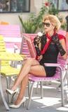 Trendig dam med den lilla svarta klänningen och rött halsduksammanträde på stol i restaurangen, utomhus- skott i solig dag Ung bl Royaltyfri Fotografi