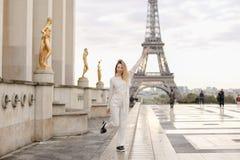 Trendig dam som går på Trocadero den fyrkantiga near förgyllda statyer och Eiffeltorn Fotografering för Bildbyråer