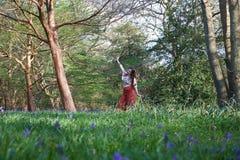 Trendig dam som poserar i ett engelskt trä med blåklockor och träd arkivbilder