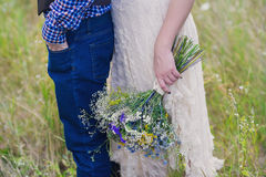 Trendig flicka för unga sunda par i en bröllopsklänninggrabb i ett anseende för plädskjorta med en bukett av ljusa blommor i händ Royaltyfri Foto