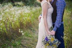 Trendig flicka för unga sunda par i en bröllopsklänninggrabb i ett anseende för plädskjorta med en bukett av ljusa blommor i händ Arkivfoton
