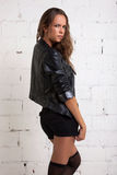 Trendig flicka i ett omslag, kortslutningar och strumpor Vit tegelstenvägg som inte isoleras Arkivfoton