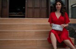 Trendig flicka i röda drees som rymmer påsen för lädersnakeskinpytonorm, elegant dräkt Modell nära den dyra villan royaltyfri bild