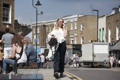 Trendig flicka i rosa solglasögon som talar på telefonen som går ner den gataBroadway vägen Arkivbild