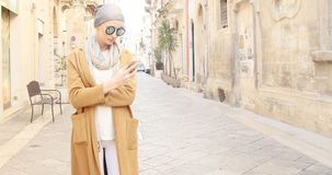 Trendig flicka med mobiltelefonen Royaltyfri Foto