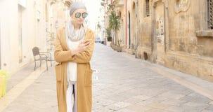 Trendig flicka med mobiltelefonen Arkivfoto