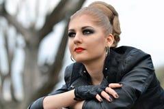 Trendig flicka med stora gröna ögon, smokeymakeupögon, röda kanter med det svarta läderomslaget och handskar utomhus arkivbilder