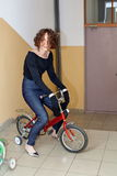 Trendig flicka på en cykel för barn` s Arkivfoton