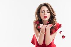 trendig flicka som blåser på hjärta formade konfettier arkivfoton