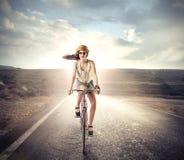 Trendig flicka som rider en cykel Arkivfoton
