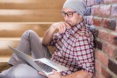 Trendig freelancer som i regeringsställning som sitter på trappa bygger och ser bärbar datorskärmen arkivfoton