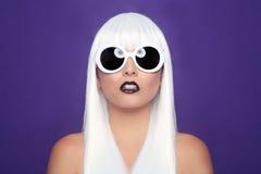 Trendig härlig kvinna som bär en utformad perukCloseup Arkivfoto