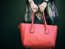 Trendig härlig stor röd handväska på armen av flickan i en trendig svart klänning som poserar nära den svarta väggen på en varm s royaltyfria foton