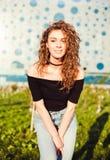 Trendig härlig ung flicka med långt hår i en svart överkant och jeans som poserar i den varma aftonen för parkerasommar ungdom Fotografering för Bildbyråer