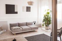 Trendig industriell lampa bredvid den scandinavian soffan i ljus vardagsrum royaltyfri bild