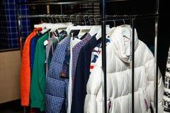Trendig kläder för visningslokal som hänger på kuggar royaltyfri foto