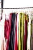 Trendig kläder hänger i lagret arkivfoto