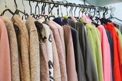 Trendig kläder på hängare i ett lager Arkivfoto