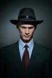 Trendig kriminalare för ung man i en stilfull hatt royaltyfria bilder