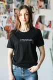 Trendig kvinna i en svart t-skjorta som poserar i en studio arkivfoto