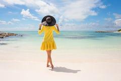Trendig kvinna med den svarta sommarhatten och den gula klänningen på stranden Royaltyfria Bilder