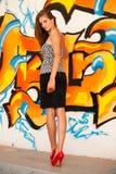 Trendig kvinna med en blured graffitti i bakgrund Arkivbilder