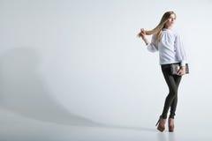 Trendig kvinna med en påse i ljus bakgrund Royaltyfri Foto