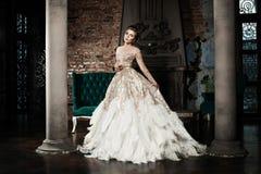 Trendig kvinna som bär den guld- klänningen Royaltyfri Fotografi