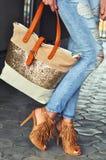 Trendig kvinna som bär sandaler för hög häl med frans, jeans och påsen Arkivfoto