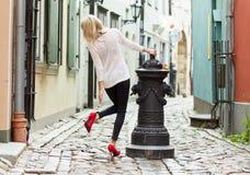 Trendig kvinna som bär röda skor för hög häl i gammal stad Arkivfoto