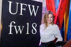 Trendig kvinna som poserar mot logoen av utställningbesökarna på en modeshow som visar arkivbild