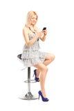 Trendig kvinna som smsar på en mobiltelefon Arkivfoto